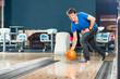 Junger Mann beim Bowling in Bowlingbahn