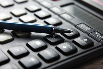Closeup image of calculator keyboard and pen