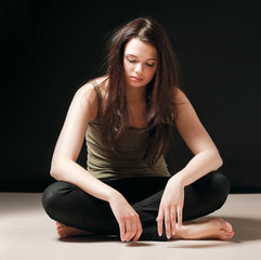 Depressed woman sitting on floor isolated on black background