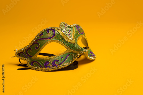 Green and gold Mardi Gras, venetian mask on Yellow background