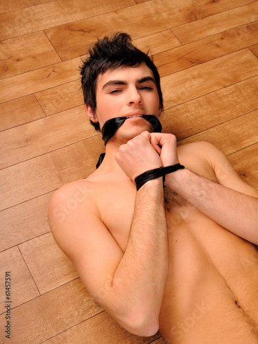 Binding nude man on a wooden floor.