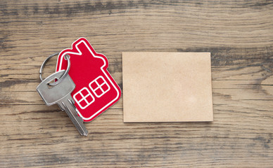 Key with house icon and blank paper on wooden background