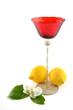 Limoni e bicchiere rosso su fondo bianco