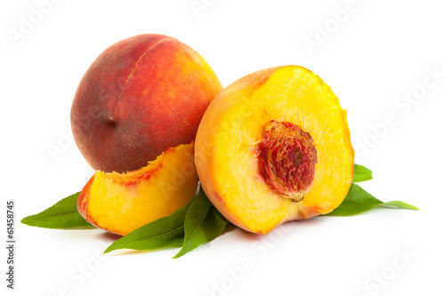 Three perfect, ripe peaches with a half  and slices isolated on