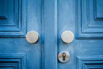 Elegant door handle on a blue vintage painted door