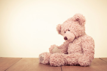 Retro Teddy Bear toy alone on wooden floor