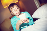 Beautiful blond child playing tablet pc lying on bed