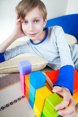 Cute happy child lying on a sofa playing with cubes