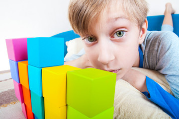 Funny little boy lying on a sofa playing with colorful cubes