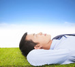 young businessman lying on a meadow and contemplating
