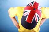 Boy in a yellow t-shirt wearing baseball cap with Union jack