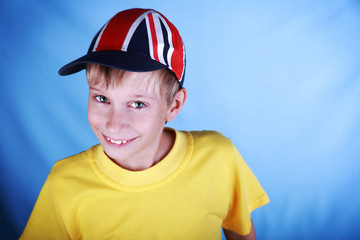 Cute blond boy wearing a baseball cap with Union Jack