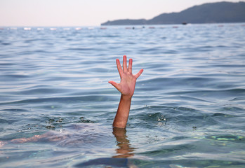 Help concept of a hand stretching out of the water in the sea