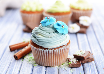 Tasty cupcakes with butter cream, on color wooden background
