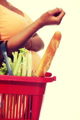 Pregnant woman doing shopping basket