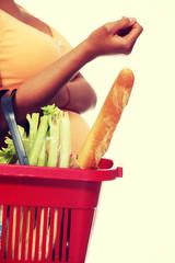 Pregnant woman doing shopping basket