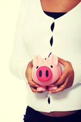 Pregnant woman holding piggy