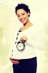 Pregnant woman with an alarm clock.