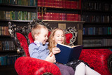 Children reading book at home