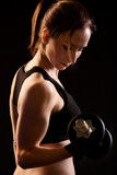 Beautiful woman with dumbbells on black background.