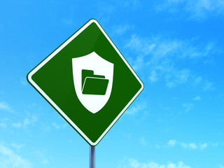 Business concept: Folder With Shield on road sign background