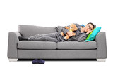 Young man in pajamas sleeping on couch with teddy bear