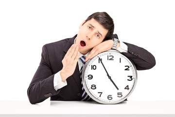 Young businessman falling asleep on a big wall clock