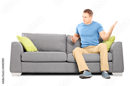 Angry man sitting on couch and violently swinging his hand