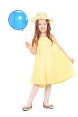 An adorable little girl in yellow dress holding blue balloon