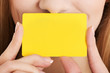 Empty yellow personal card over woman's face.