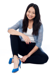 Fashionable smiling girl sitting on the floor