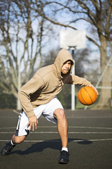 Portrait of a Hooded Basketball Player bouncing the ball