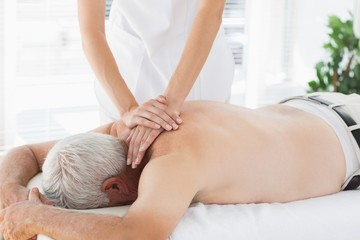 Therapist massaging back of senior patient