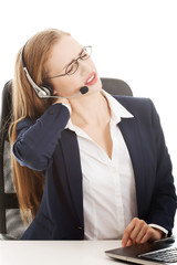Beautiful business woman at call center is having back ache.