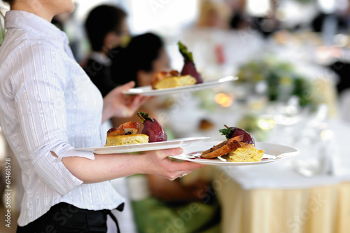 Waitress is carrying three plates