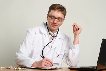 doctor with stethoscope working on a laptop