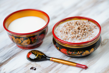 Buckwheat with milk in khokhloma tableware, close-up