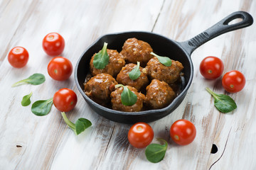 Meatballs with cherry tomatoes and corn salad leaves