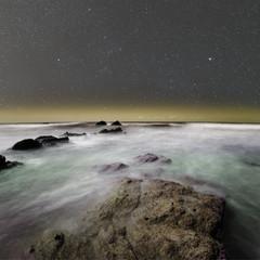 Rugged coast under the night sky.
