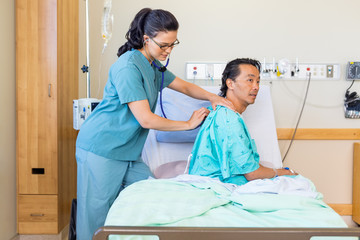 Nurse Examining Male Patient's Back With Stethoscope On Hospital