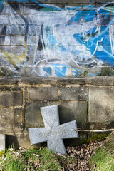 cross headstone leaned against graffiti filled wall