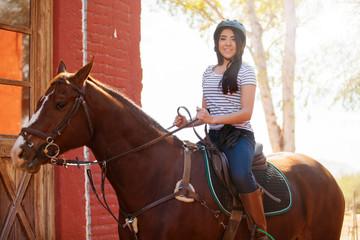 Cute Latin girl riding a horse