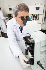 Male Researcher Using Microscope In Lab