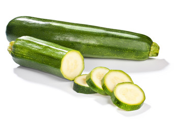 Fresh whole chopped green zucchini isolated on white