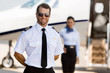 Pilot Standing With Stewardess And Private Jet At Terminal - 61470557
