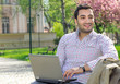 Happy man sitting on bench and using laptop