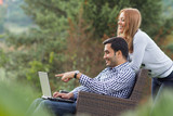 Couple or friends using laptop poster