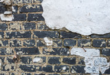 Closeup of an old white plastered brick wall