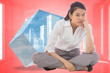 Composite image of grumpy businesswoman sitting cross legged
