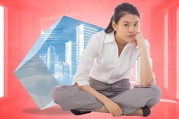 Composite image of grumpy businesswoman sitting cross legged